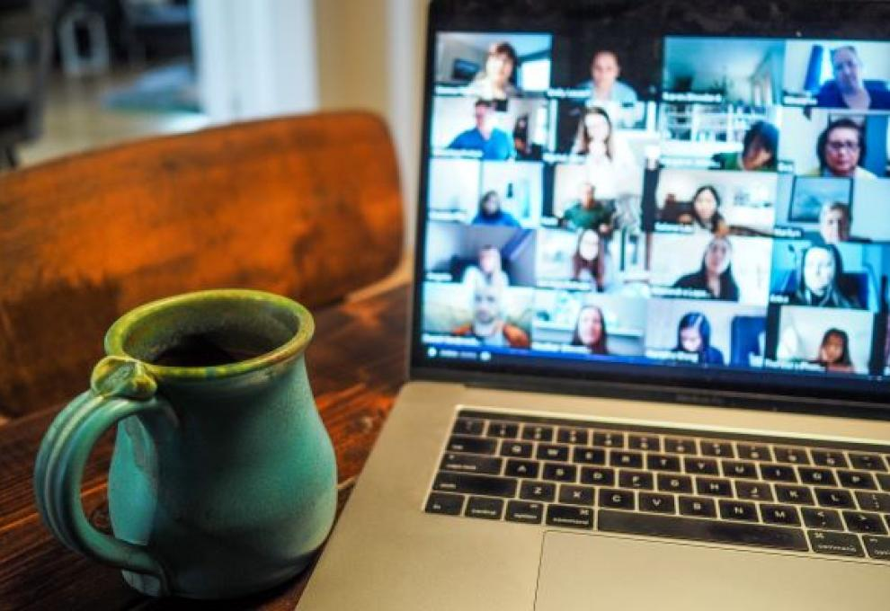 A laptop displaying a zoom call with a blue mug placed next to it