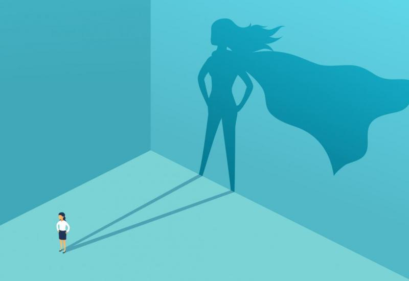 A woman illuminated with a superhero shadow