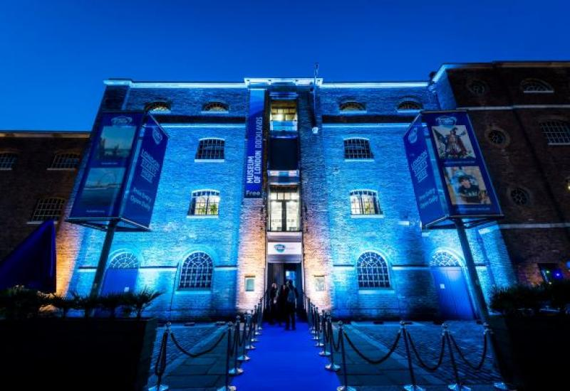 The outside of Museum of London Docklands at night, illuminated by blue light